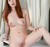 Redhead poses nude on windowsill with white curtain