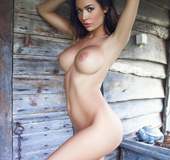 Beautiful flower girl with big boobs goes naked outside a wooden cabin
