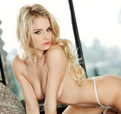 Young all natural blond in white lingerie and creame heels poses in the