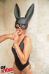 Tattoed gal in black bodysuit and bunny mask masturbating on the black