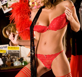 Splendid blonde wearing a red undergarment and stockings with black scarf