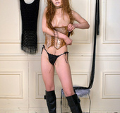 Redhead with smooth pinkish skin wears leather boots while naked modelling