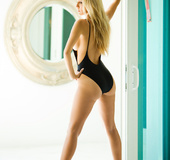 Beautiful blue eyed blond in a black one piece swimsuit and heels poses