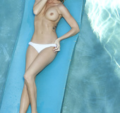 Hot blonde with blue eyes in the pool wearing white undies and covers