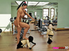 Two male midgets are manhandled by an exotic brawny babe at the gym.