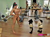 Ponytailed giantess at the gym dominates two male midget wrestlers.