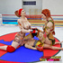 Tattooed female wrestlers give a male boxer a face full of feet.