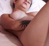 Tattooed hottie with low hanging breasts rubs hairy pussy, then uses dildo