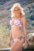 A petite blonde, wearing a poke-a-dot bikini, shows off her body for the