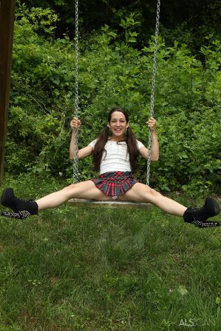 petite girl plays swing