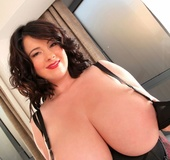 A busty slut wearing all black shows us her massive tits with a smile