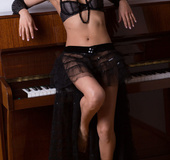 Brunette wife with a transparent black skirt and black beads around her
