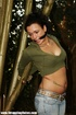 Lusty brunette in jeans pants and green top gagged and tied to bamboo