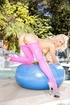 Topless blonde in pink leggings posing near the pool