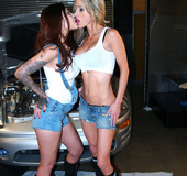 Sexy chicks in jean shorts and black boots kiss and touch in an auto shop.