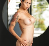 Swarthy exotic girl with tattoos and braids posing nude