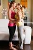 Blonde takes off her brunette partner's black yoga pants