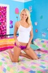 Blonde teen in white top and miniskirt teasing on the bed and showing
