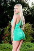 Petite blonde in black heels and short green dress posing outdoors and