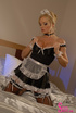 Luring blonde in black and white housekeeping outfit confident in her