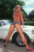 This mature blonde strikes a pose next to a sexy sports car