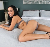 Goddess gets rid of her gray panties before spreading her pussy in bed.
