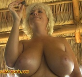 Short-haired, blue-eyed blonde topless at a swingers resort