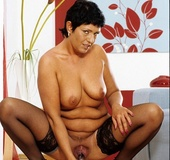 Indulging granny with fat body lays down naked on a blue couch and shows