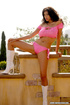 Brunette in pink shows off her ass on the balcony.