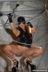 Hot brunette in latex shows her shaven pussy in the chain room.