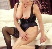 Blonde granny shows her large breasts and nasty pussy as she pose her