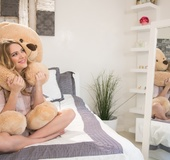Blonde slut shows her long legs having fun with a stuffed bear.