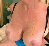 Big boobed granny in stockings and blue lingerie masturbating on the bed