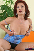 Redhead granny with blue eyes pulls aside her black panty and blue dress