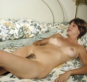 Busty brunette with hairy coochie teasingly posing nude on the bed