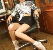 Slender body brunette in black miniskirt and white socks teasingly posing