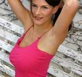 High heeled brunette in pink top and striped miniskirt flashing her white