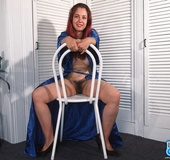 Busty redhead in blue gown and black heels posing on the white chair before