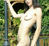 Slender brunette with big naturals sheds black outfit and undies outdoors