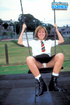 Big boobed redhead in black boots and school girl uniform undressing on