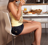 Busty brunette in miniskirt sheds yellow top and black panty in the kitchen