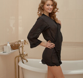 Big tits bimbo with curly hair teasing in the bathroom in black gown and