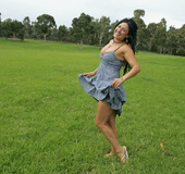 Cute chick displays her alluring body in different poses in a grassy field