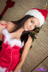 Sexy brunette wearing skimpy santa outfit with white fishnet stockings