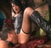Black haired chick in leather corset and fishnet hose gets her pussy licked