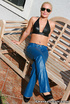 Pierced belly blonde in sunglasses and blue leather pants sheds black