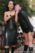 Black haired harlot in leather skirt and corset dominating naked guy outdoors