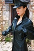 Red lipped brunette in black leather coat and cap exposing her tits under