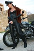 Red lipped mistress in leather outfit and fur teasing outdoors before