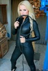 High heeled blonde in black leather bodysuit exposing her big tits before